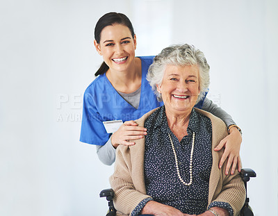 Buy stock photo Portrait of a caring young nurse posing with her elderly patient as she sits in a wheelchair in a healthcare center