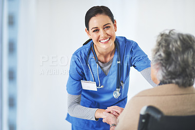 Buy stock photo Portrait of a friendly young nurse chatting with her elderly patient while she sits in a wheelchair in the healthcare center
