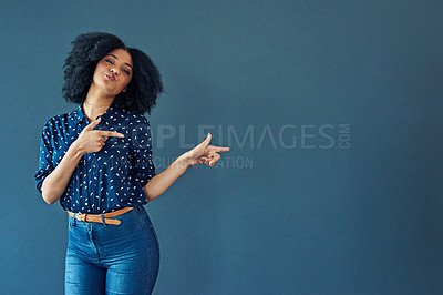 Buy stock photo Studio shot of a young woman pointing towards copy space against a gray background