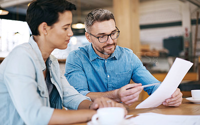 Buy stock photo Shot of a man and woman going through paperwork together in a coffee shop