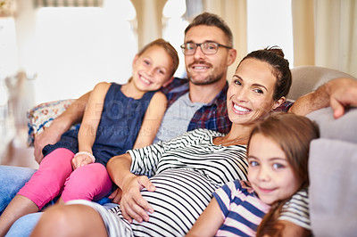 Buy stock photo Portrait of a happy young family posing on their sofa at home