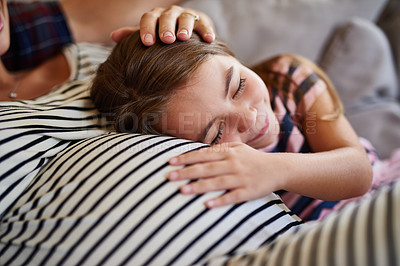 Buy stock photo Shot of a young girl cuddling her pregnant mother's stomach