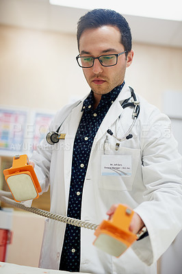 Buy stock photo Shot of a doctor using a defibrillator in a hospital