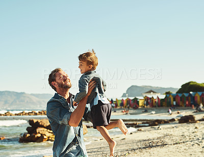 Buy stock photo Shot of a young Father tossing his son into the air at the beach
