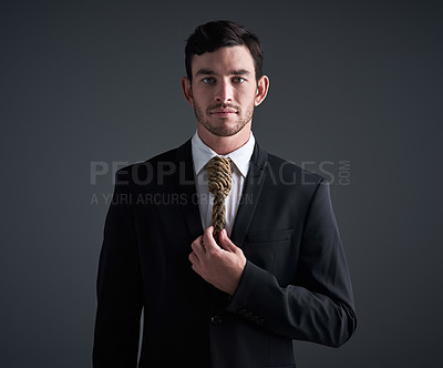 Buy stock photo Studio portrait of a young businessman with a noose tied around his neck for a tie against a gray background