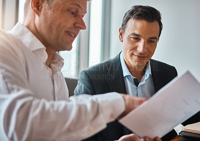 Buy stock photo Shot of two mature businessmen discussing paperwork in a corporate office