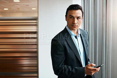 Buy stock photo Shot of a well-dressed businessman using his cellphone at the office