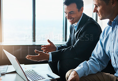 Buy stock photo Shot of two businessmen having a discussion while sitting by a laptop