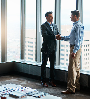 Buy stock photo Shot of two businessmen shaking hands in a corporate office
