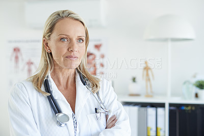 Buy stock photo Shot of a confident mature doctor working in a consulting room