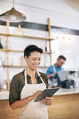 Buy stock photo Shot of a young woman using a digital tablet in a coffee shop with her coworker in the background