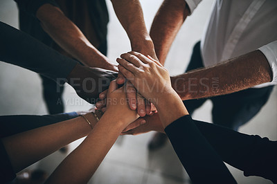 Buy stock photo Cropped shot of a group of colleagues joining their hands in solidarity during a late night at work