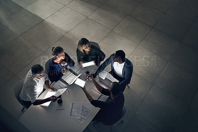 Buy stock photo Shot of a group of colleagues having a meeting during a late night in a modern office