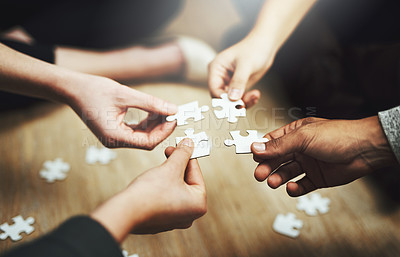 Buy stock photo Cropped shot of a group of unrecognizable people fitting puzzle pieces together on the floor