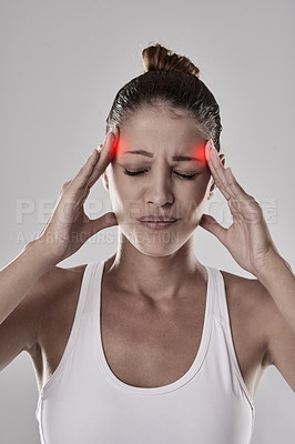 Buy stock photo Studio shot of an athletic young woman holding her head in pain against a grey background