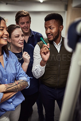Buy stock photo Shot of a group of designers brainstorming on a whiteboard in an office