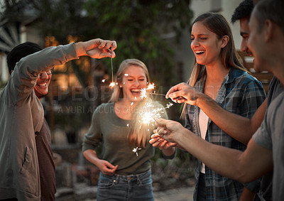 Buy stock photo Shot of a group of cheerful young friends having fun with sparklers together outside at night