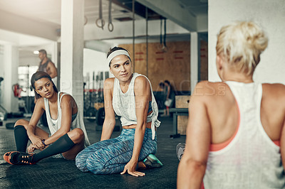Buy stock photo Shot of a group of young women taking a break together after a workout at the gym