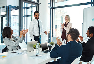 Buy stock photo Shot of businesspeople applauding a colleague in an office