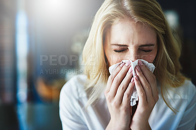 Buy stock photo Shot of a frustrated businesswoman using a tissue to sneeze in while being seated in the office