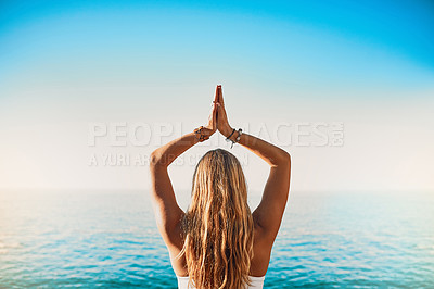 Buy stock photo Rearview shot of a young woman practicing yoga on the beach
