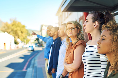 Buy stock photo Shot of a group friends standing and looking into the distance next to a street outside