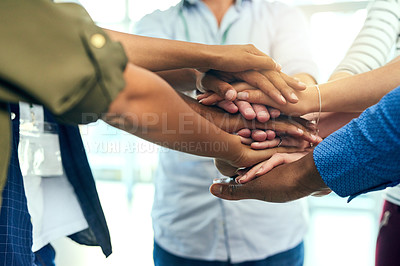 Buy stock photo Shot of a group unrecognizable people putting their hands together in a huddle in side of a building
