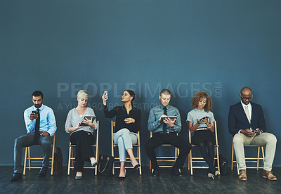 Buy stock photo Shot of a group of business people using their smart devices while waiting to be interview