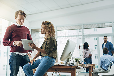 Buy stock photo Shot of two young colleagues using a digital tablet together in a modern office