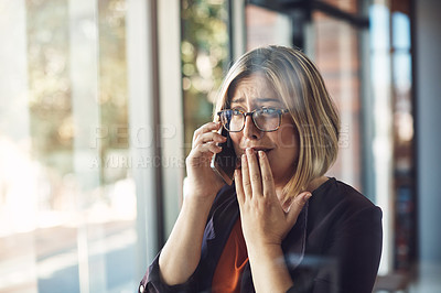 Buy stock photo Shot of a young woman looking distraught while talking on a mobile phone in a modern office