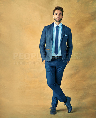 Buy stock photo Studio shot of a handsome young businessman posing against a golden background