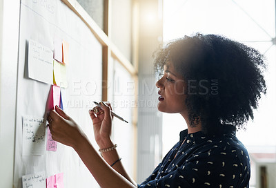 Buy stock photo Shot of a young female designer working in her office