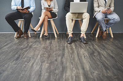 Buy stock photo Shot of a group of unrecognisable businesspeople waiting in line for a job interview
