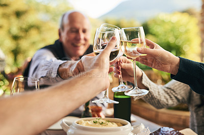 Buy stock photo Shot of a group of cheerful people celebrating with a toast over a dinner table outside