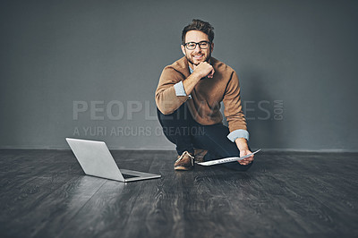 Buy stock photo Studio portrait of a young businessman working on a laptop against a grey background