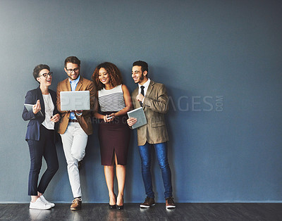 Buy stock photo Studio shot of a group of businesspeople using wireless technology together while standing in line against a gray background