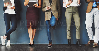 Buy stock photo Cropped studio shot of a group of businesspeople using wireless technology while waiting in line against a gray background