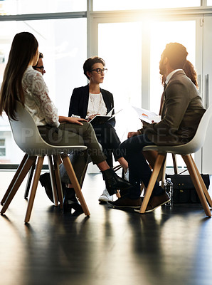 Buy stock photo Shot of a group of corporate businesspeople sitting in a meeting