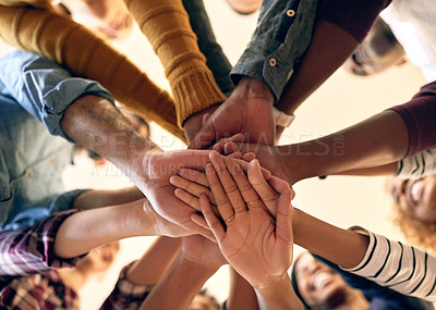 Buy stock photo Low angle shot of a group of people joining their hands together