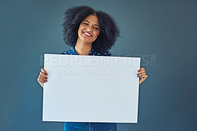 Buy stock photo Studio shot of a young woman holding up a blank placard against a gray background