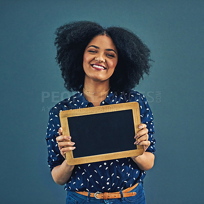 Buy stock photo Studio shot of a young woman holding a blank chalkboard against a gray background