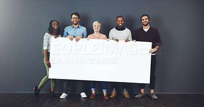 Buy stock photo Studio shot of a diverse group of people holding a blank placard against a gray background