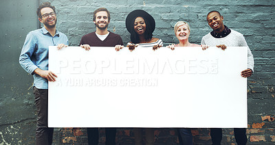 Buy stock photo Shot of a diverse group of people holding a blank placard against a gray brick wall