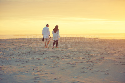 Buy stock photo Rearview shot of an affectionate mature couple walking on the beach