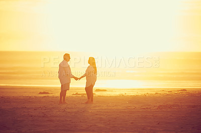 Buy stock photo Full length shot of an affectionate mature couple standing face to face and hand in hand on the beach