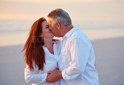 Buy stock photo Shot of a mature couple kissing on the beach