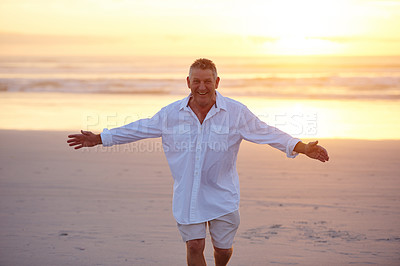 Buy stock photo Cropped portrait of a handsome mature man standing with his arms outstretched on the beach at sunset