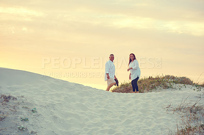 Buy stock photo Shot of mature people standing on a sand dune at the beach