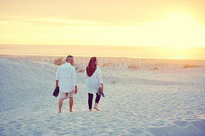 Buy stock photo Shot of a mature couple going for a relaxing walk on the beach