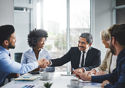 Buy stock photo Shot of two businesspeople shaking hands in a meeting